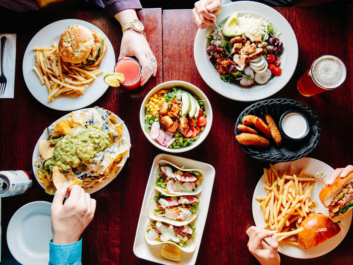 Overhead view of a table of American comfort food, such as a burger and fries, with hands reaching in to grab food and drinks. There are also cans of beer and cocktails on the table.