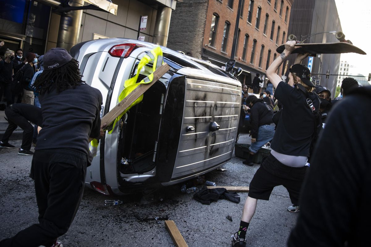 Protesters damage an overturned Chicago Police Department SUV on Kinzie near State as thousands in Chicago joined national outrage over the killing of George Floyd in Minneapolis police custody, Saturday afternoon, May 30, 2020.