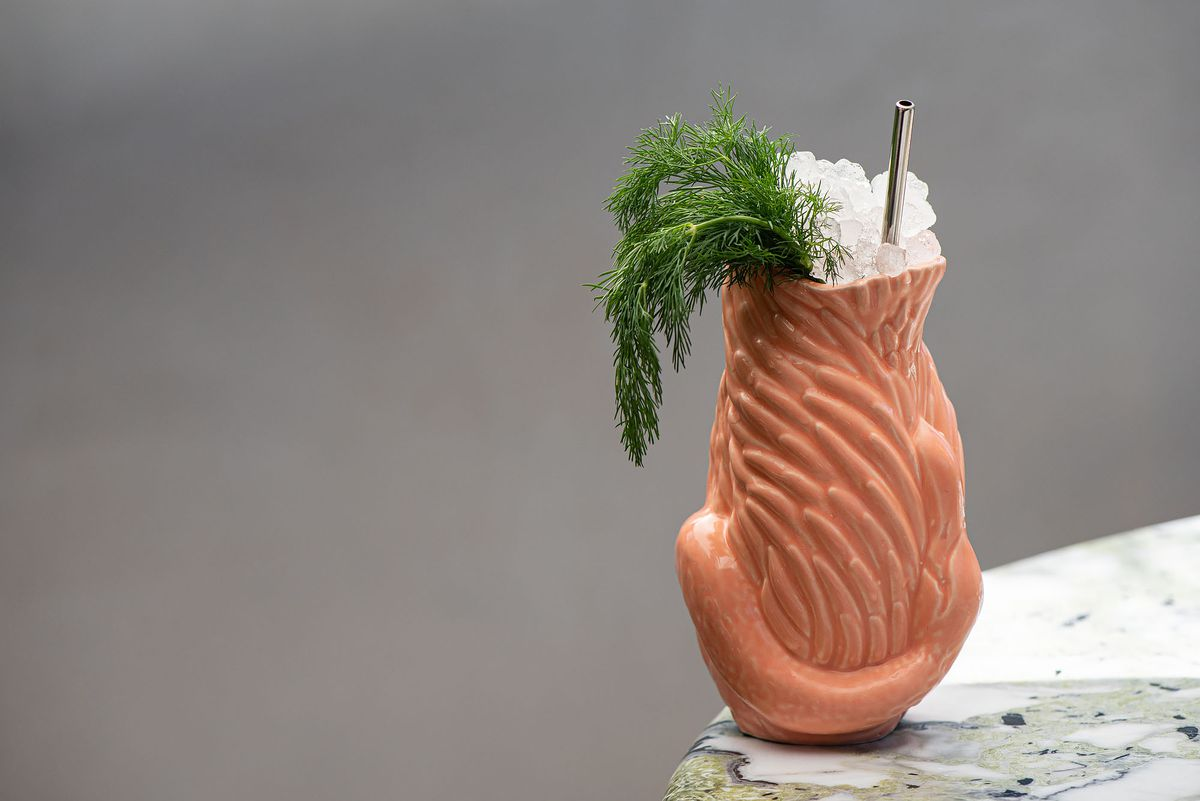 A cocktail with herbs sticking out.
