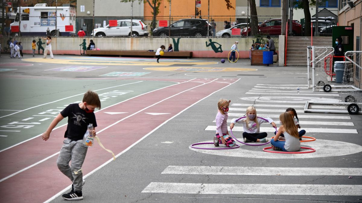 A young boy wearing a black shirt and grey pants walks along a track. Four girls play sitting within hula-hoops and many other children play in the background on a track during an after school program.
