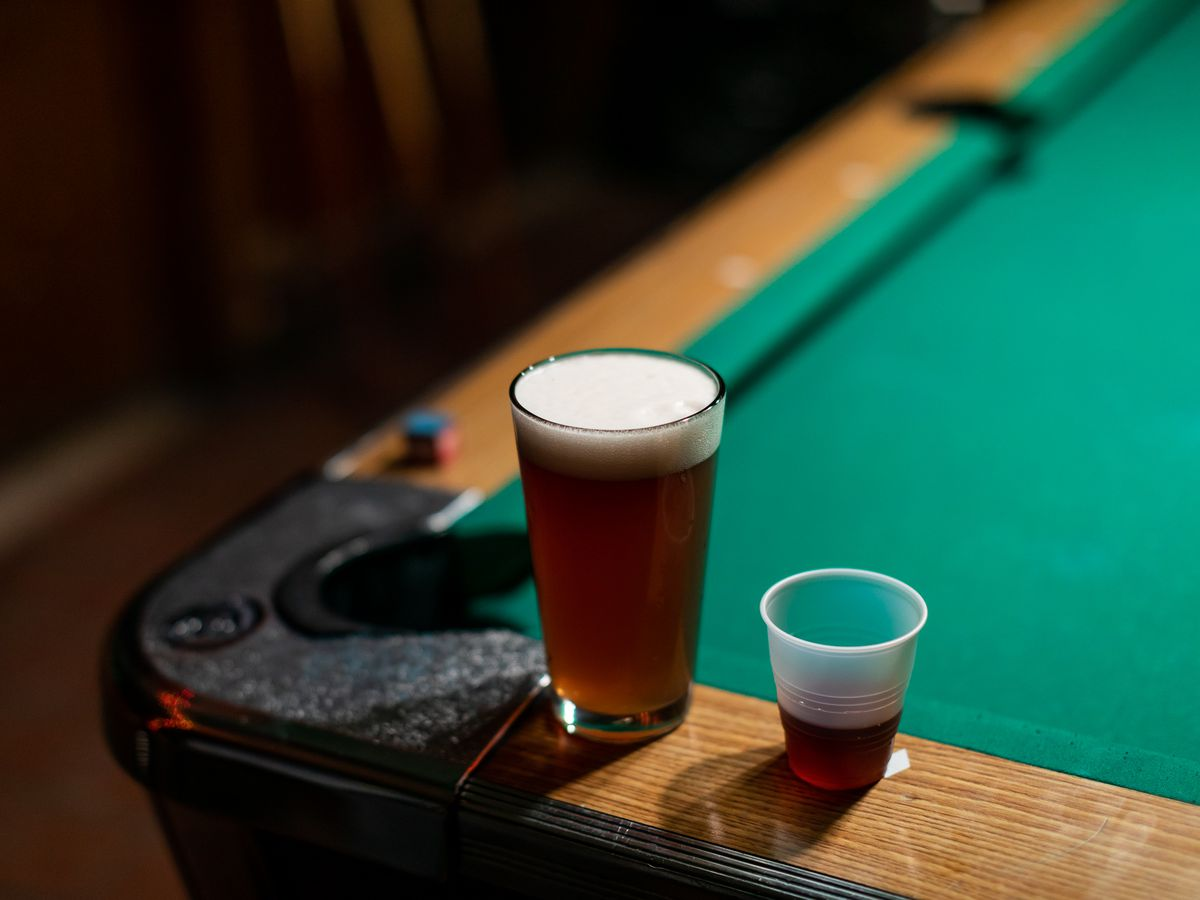An IPA in a pint glass and a plastic cup with purple jezynowka sitting on the edge of a pool table