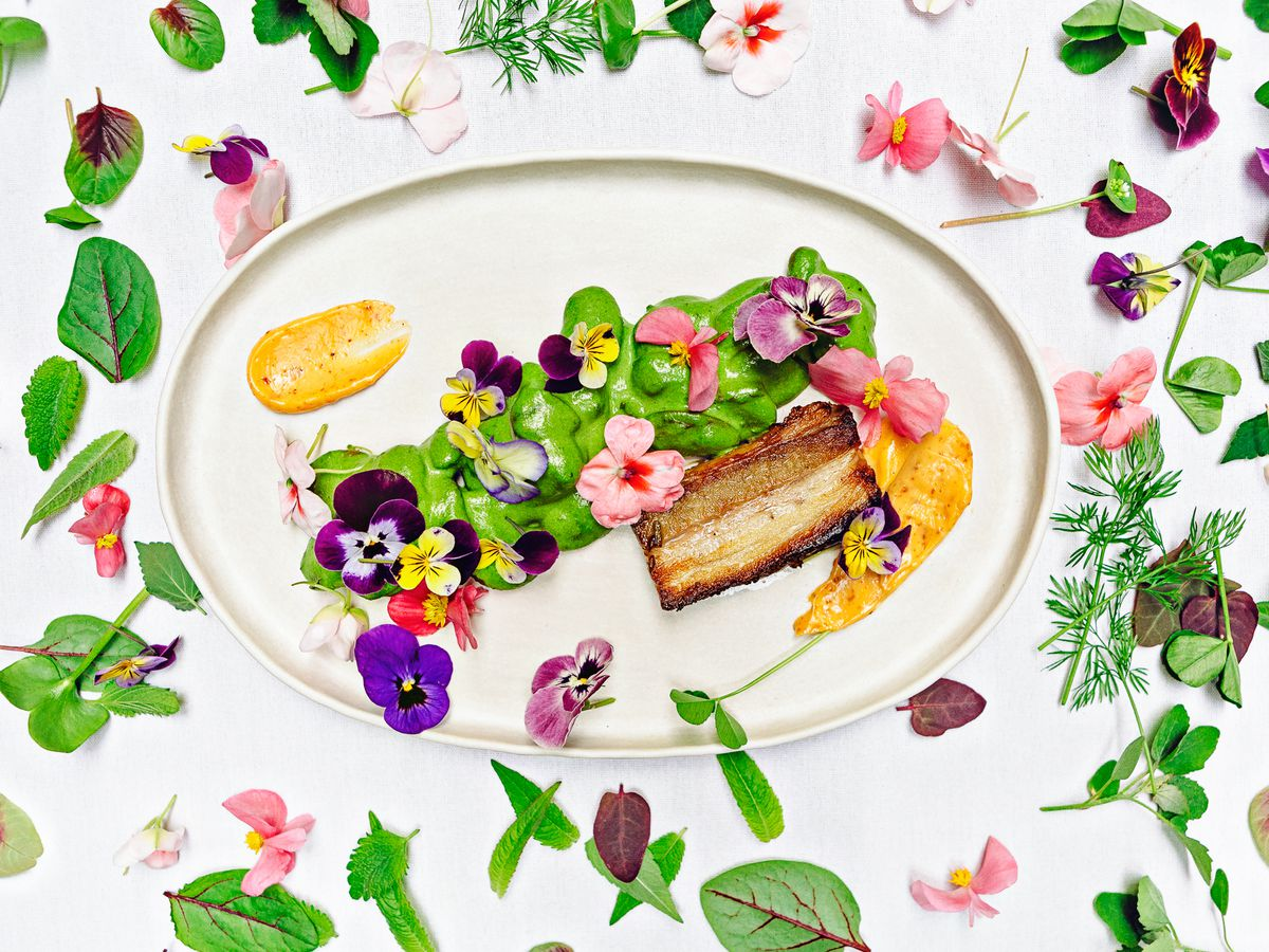 From above, a serving platter topped with a large piece of cooked meat, beside a smear of green sauce, topped with flowers. The dish is also surrounded on a white background by flowers and leaves