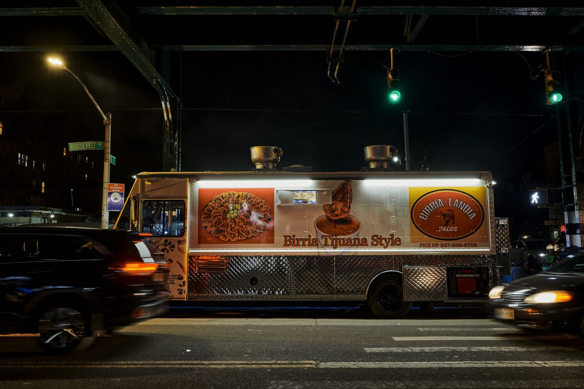 """A lengthy food truck sits under an overpass in the Queens neighborhood of Jackson Heights. There's a street sign with the word """"Roosevelt."""""""
