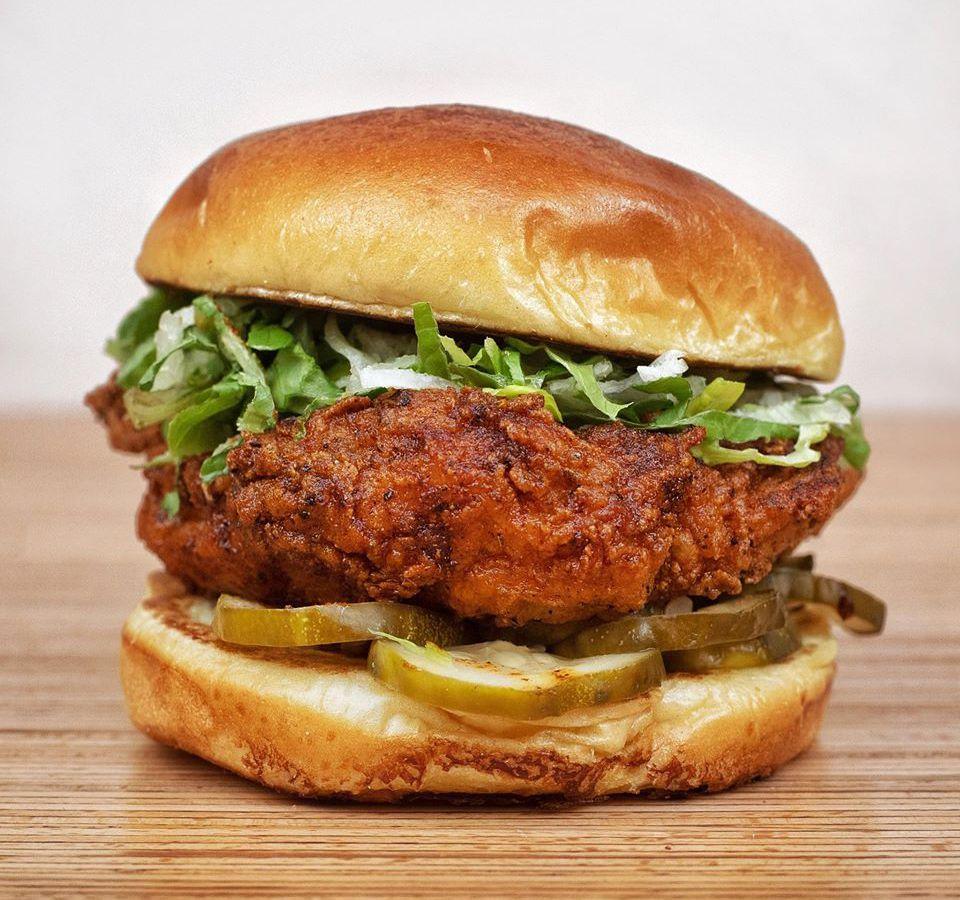 Nashville hot chicken sandwich on a wooden table
