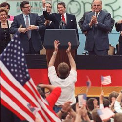 A spectator jumps up as U.S. President Ronald Reagan gives a thumbs up sign June 12, 1987 at the conclusion of his speech in front of the Brandenburg Gate in West Berlin June 12, 1987. Applaluding Reagan are West German Chancellor Helmut Kohl, right, and West German Parliament President Philip Jenninger, left. Man behind Reagan's hand is not identified. The Berlin Wall can also be seen.