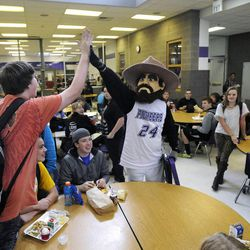 Air Force Tech Sgt. Edward Goettig dressed as the Pioneer Pete mascot at Lehi High School high-fives a student as his daughter Bailee, at right, doesn't notice him in the cafeteria on Thursday, March 6, 2014. Goettig had been deployed to Afghanistan since Aug. 27, 2013.