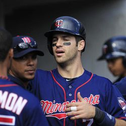 Minnesota Twins' Joe Mauer high fives his teammates after scoring during the sixth inning of a baseball game against the Detroit Tigers at Comerica Park in Detroit, Sunday, Sept. 23, 2012.