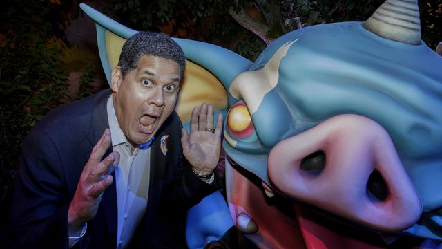 Reggie Fils-Aime makes a funny face next to an oversized statue of a bokoblin, a cartoony creature from the Legend of Zelda