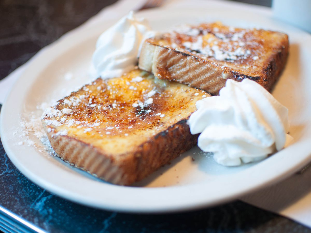 Two pieces of creme brulee French toast sit on a white plate, garnished with dollops of whipped cream