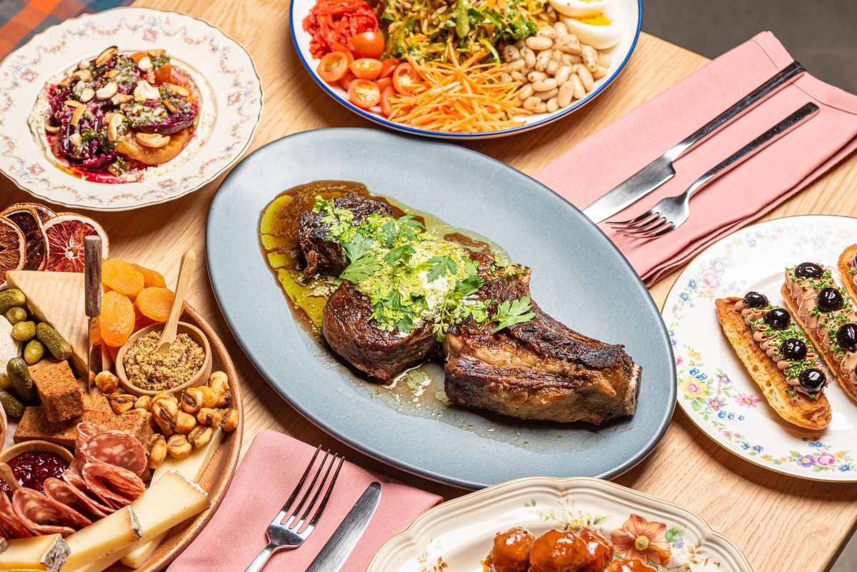 A pink tablecloth and an array of dishes from a new restaurant, including charcuterie.