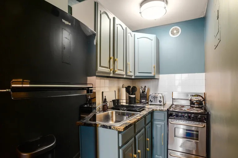 A kitchen with light blue cabinetry.