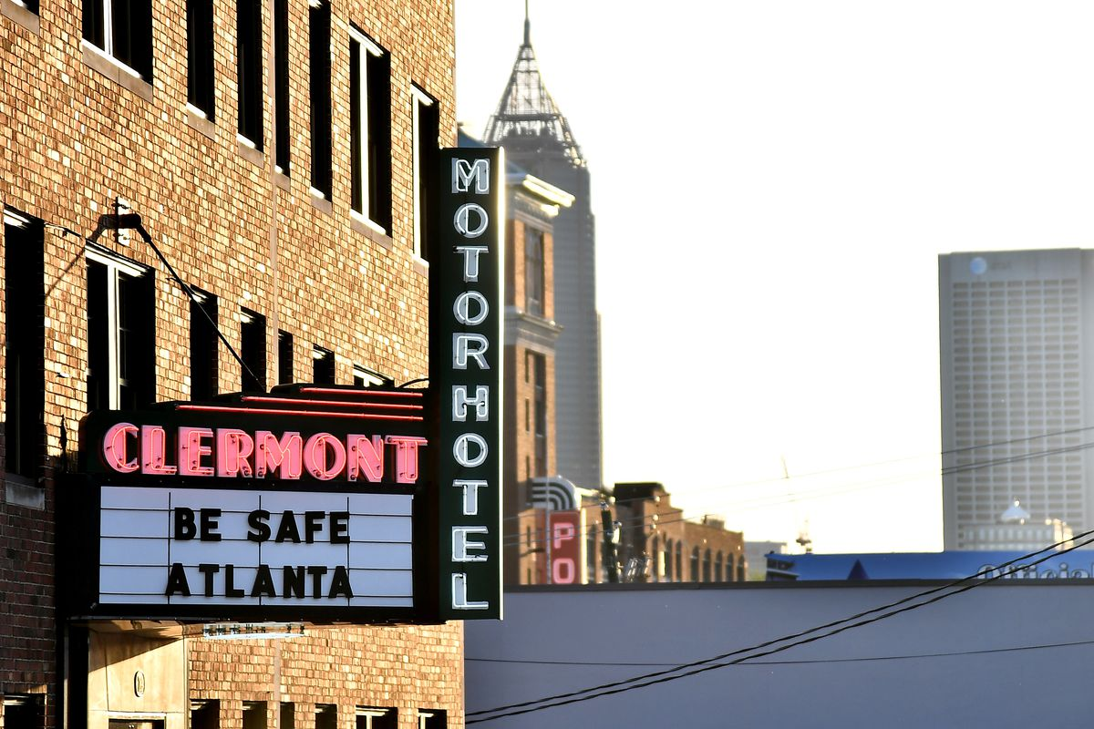 """A marquee under a neon Clermont sign reads, """"Be safe Atlanta."""" The Atlanta skyline is visible in the background."""