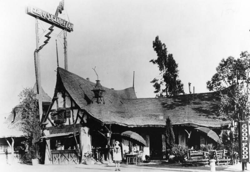 """A waitress stands in front of the thatched roof Tam O'Shanter Inn. A sign at right reads """"Good Food."""" . Two umbrellas and tables have been placed outside for outdoor dining."""