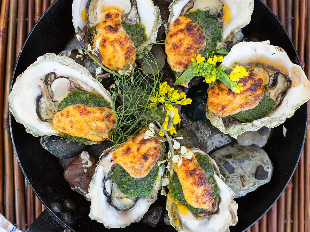 Broiled oysters in a cast iron pan topped with green and orange sauces.
