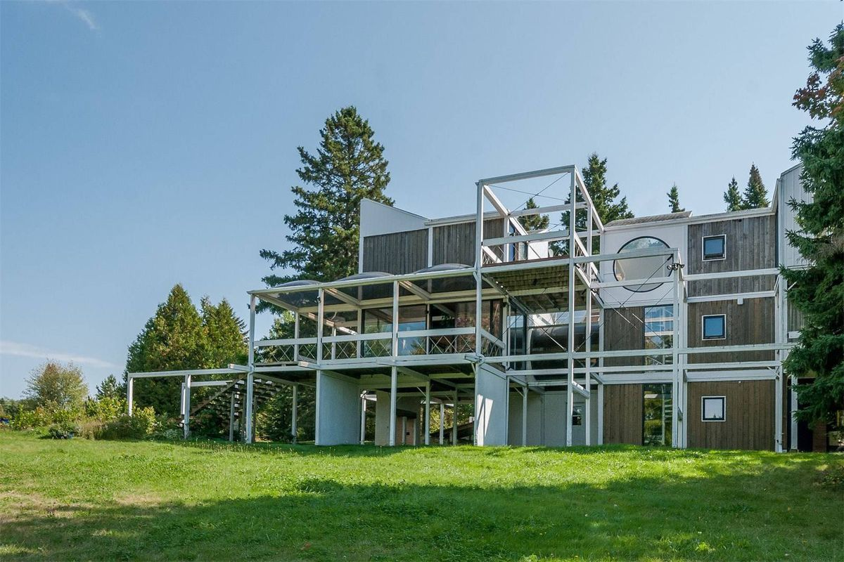Modern house formed by stacked blocks and extended beams and terraces on grassy lot.