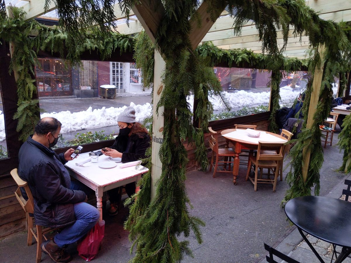 People sitting in an outdoor dining space with snow visible in the background.