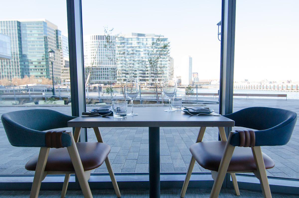 A two-top table in a restaurant sits by floor-to-ceiling windows that look out onto a waterfront area with skyscrapers in the distance