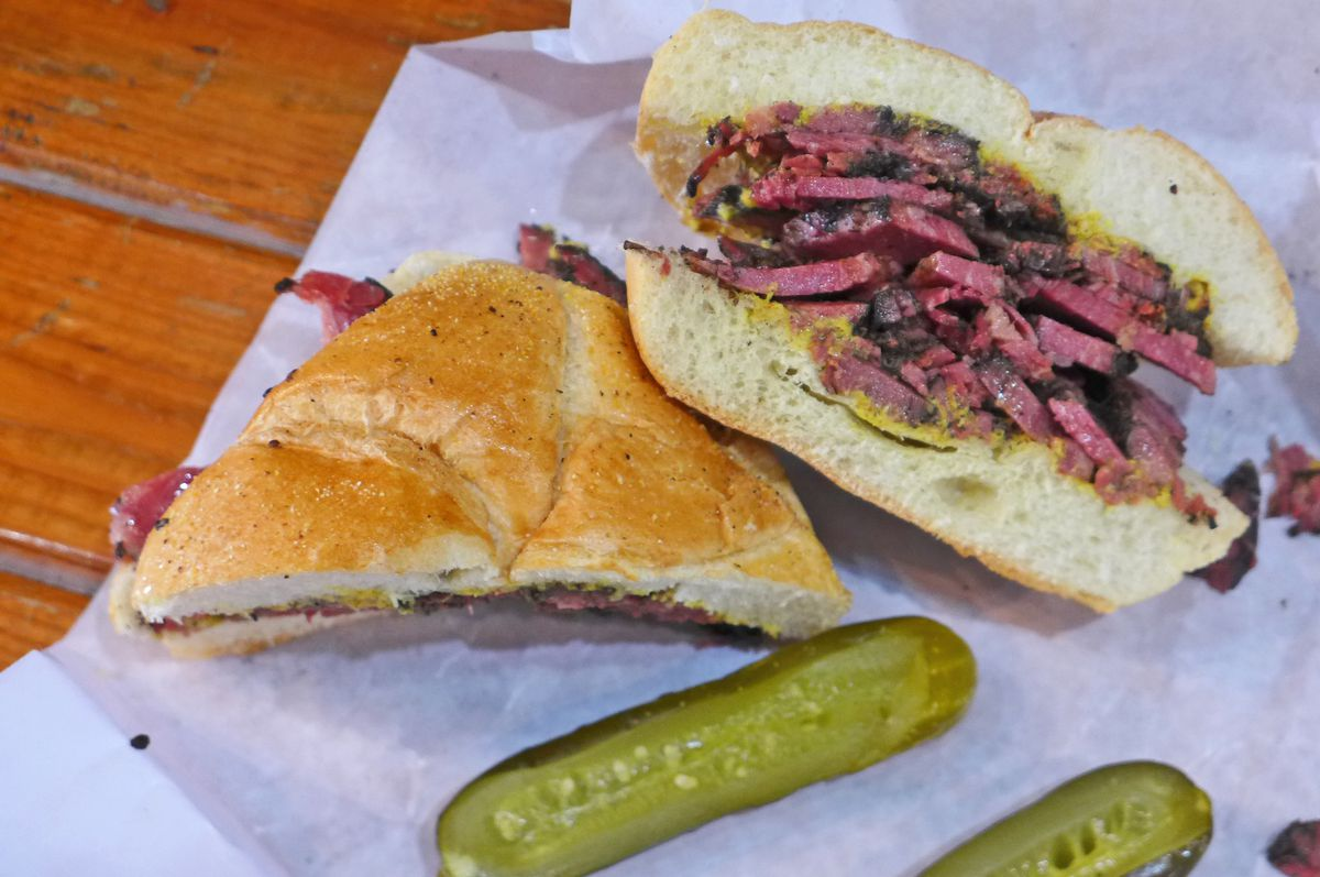 A sandwich filled with garnet colored meat sliced thick and a pair of pickle spears in the foreground.