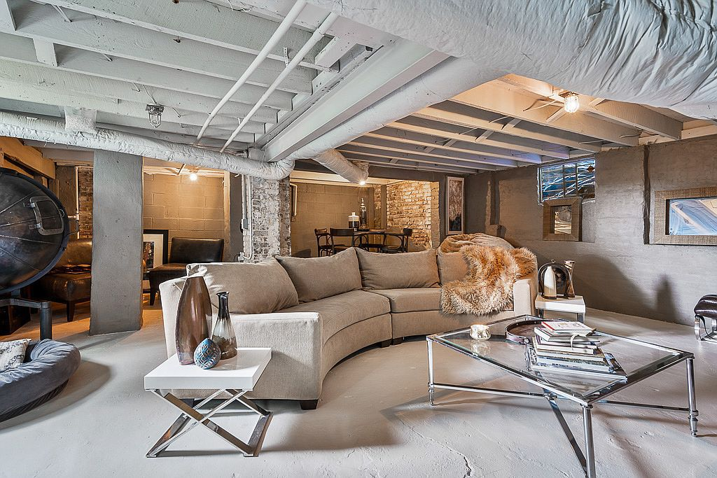 A basement with a large couch and gray walls.