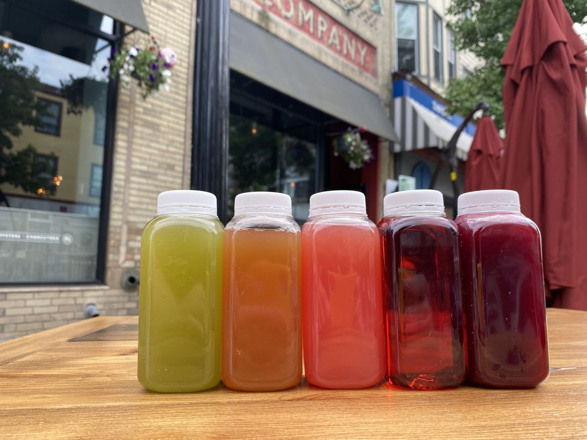 A lineup of five colorful cocktails in plastic bottles on a wooden table outdoors