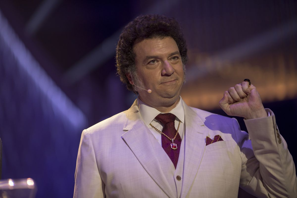 Danny McBride plays Jesse Gemstone wearing a suit, a headset microphone, and holding up his fist.
