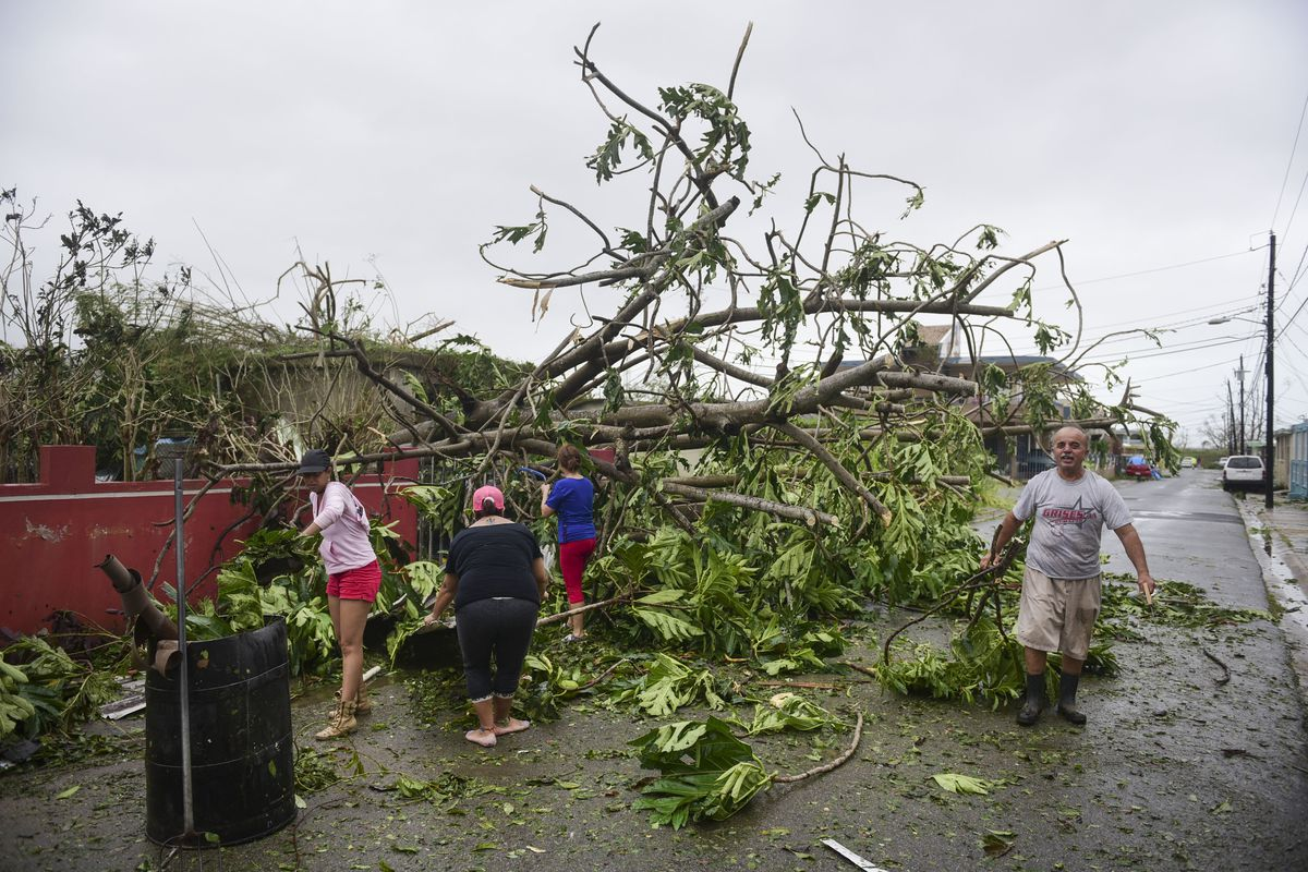 A family helps clean the road after Hurricane Maria hit the eastern region of the island, in Humacao, Puerto Rico.   Carlos Giusti/Associated Press