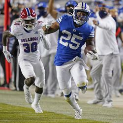 BYU running back Tyler Allgeier (25) carries the ball as Louisiana Tech defensive back Cedric Woods (30) pursues during the second half of an NCAA college football game Friday, Oct. 2, 2020, in Provo.