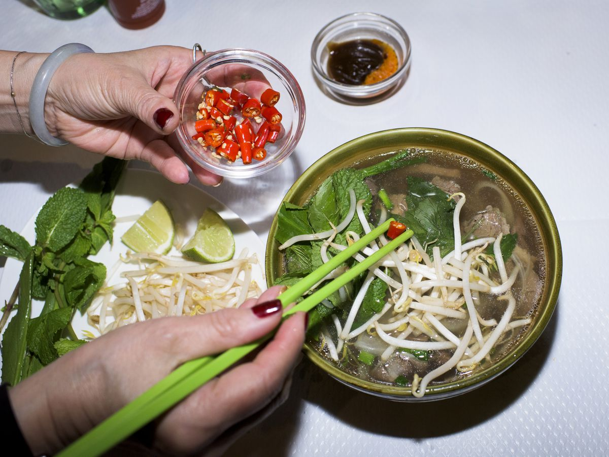 Hands add chiles to a bowl of pho with bright green chopsticks