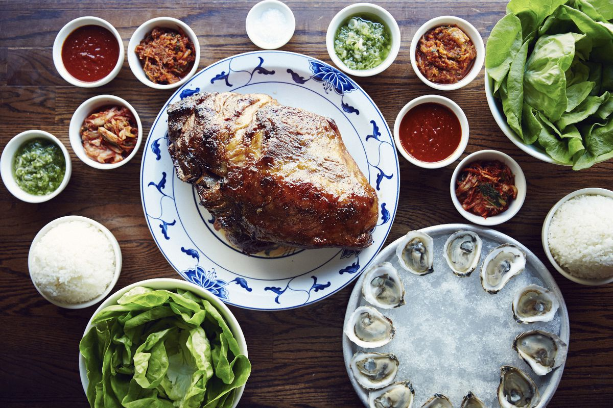 The bo ssäm pork butt at Ssäm Bar sits surrounded by oysters on the half shell, multi-colored sauces, and lettuce leaves