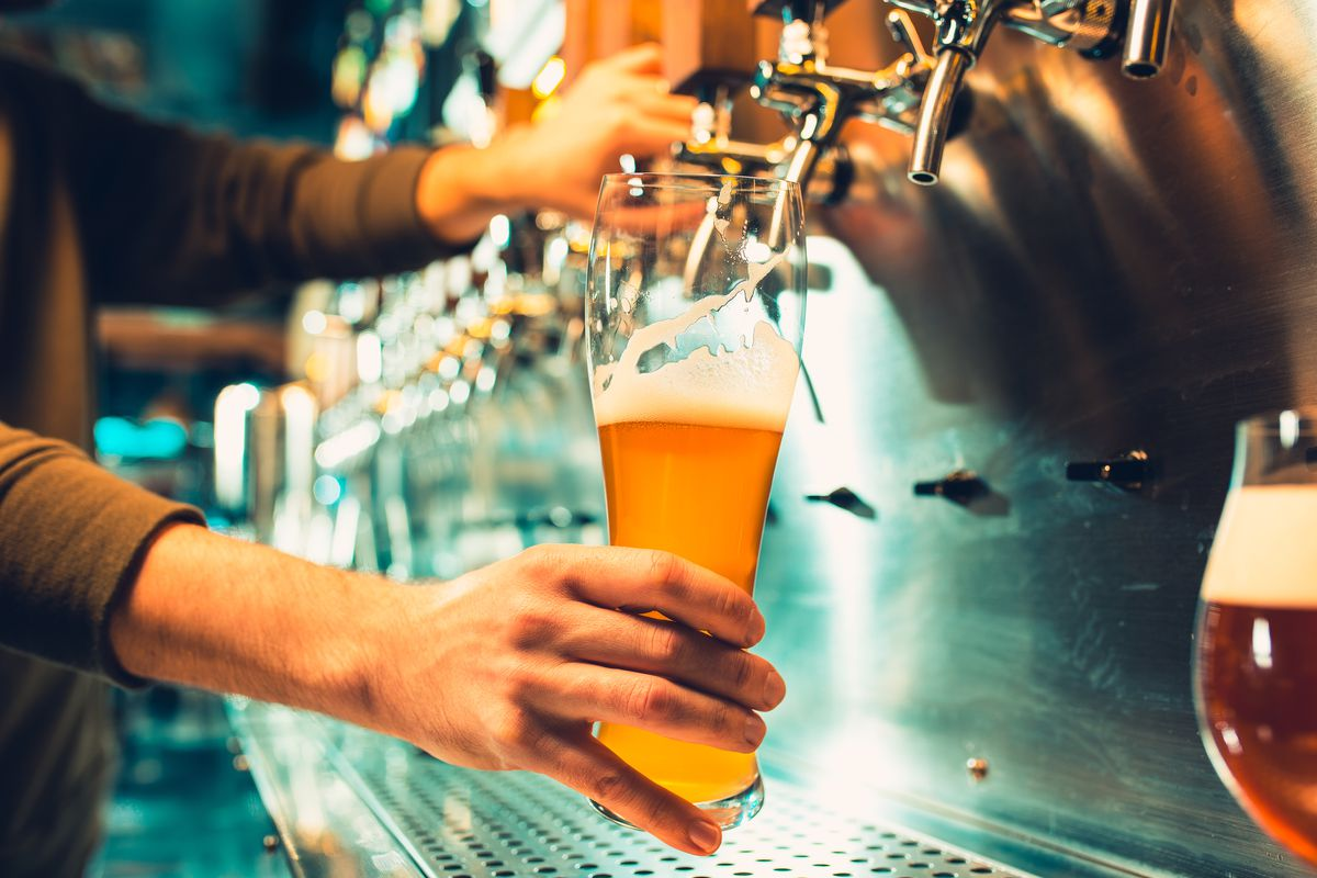 Hand holding a glass of draft beer as it is filled from a tap