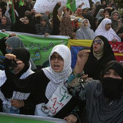 """Pakistani Shiite Muslim women chant anti U.S. slogans during a demonstration that is part of widespread anger across the Muslim world about a film ridiculing Islam's Prophet Muhammad, Sunday, Sept. 23, 2012 in Lahore, Pakistan. The woman, center, wear a banner that reads, """"at your service Hussein."""""""