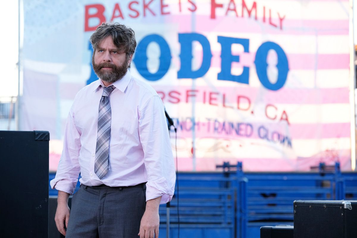 """Actor Zach Galifianakis in the FX show """"Baskets"""" standing in front of a sign that reads, """"Baskets Family Rodeo, Bakersfield, CA."""""""