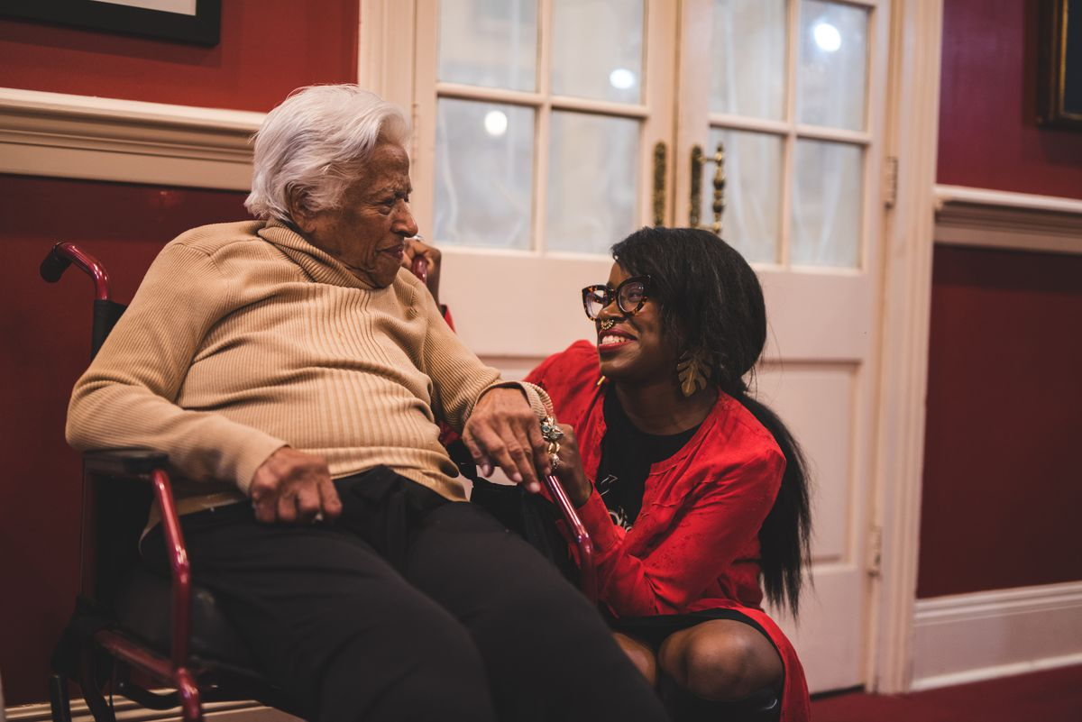 An older woman, Leah Chase, sits in a chair, while a younger woman, Ashtin Berry, kneels to her left.