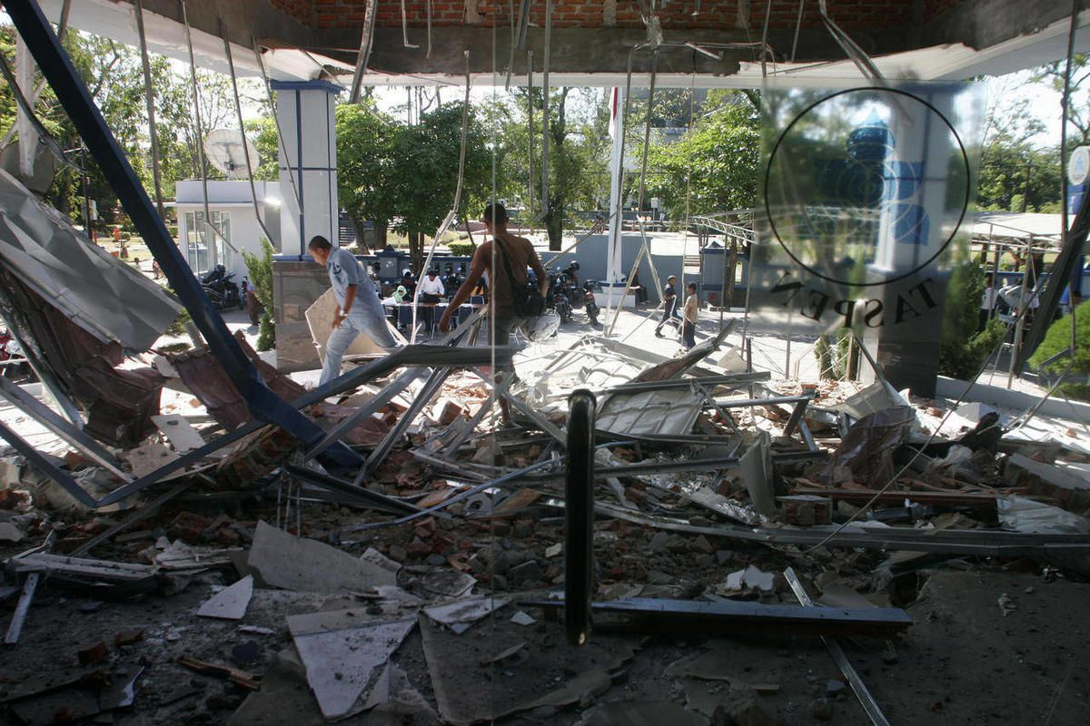People walk through debris from Wednesday's strong earthquake at an office building in Banda Aceh, Aceh province, Sumatra island, Indonesia, Thursday, April 12, 2012. Cries of panic and fervent prayers rang out Wednesday as Indonesians rushed toward high