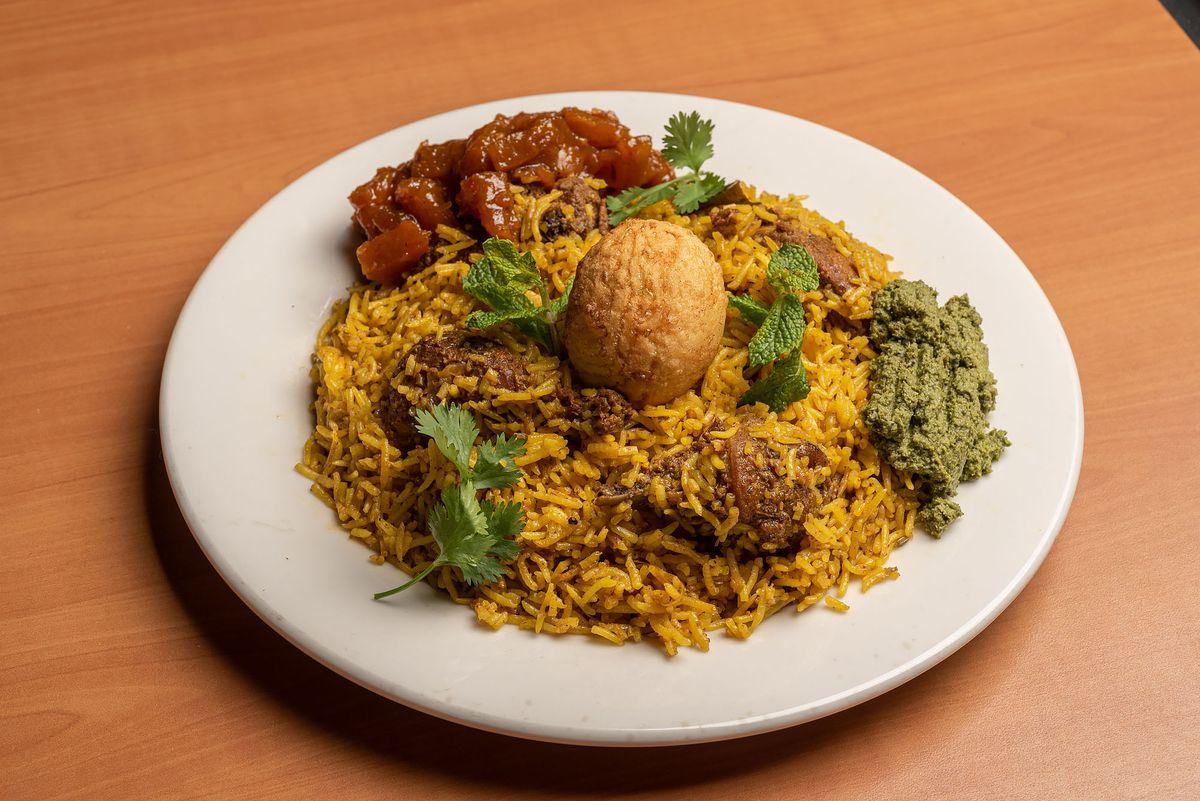 Chicken biryani on a white plate with herb garnish.