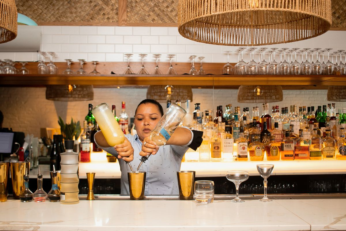 A woman stands behind Semma's bar pouring liquors into a cocktail mixer.