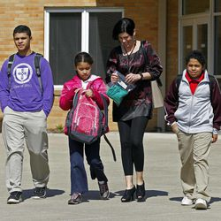 FILE - In this March 16, 2011 file photo, Heather Coffy, right center, leaves the St. Monica School with her children, left to right, Delano Coffy, 15, Alanna Marshall, 8, and Darius Coffy, 11, in Indianapolis. Students like Delano are at the heart of brewing political fights and court battles over whether public dollars should go to school vouchers to help make private schools more affordable.