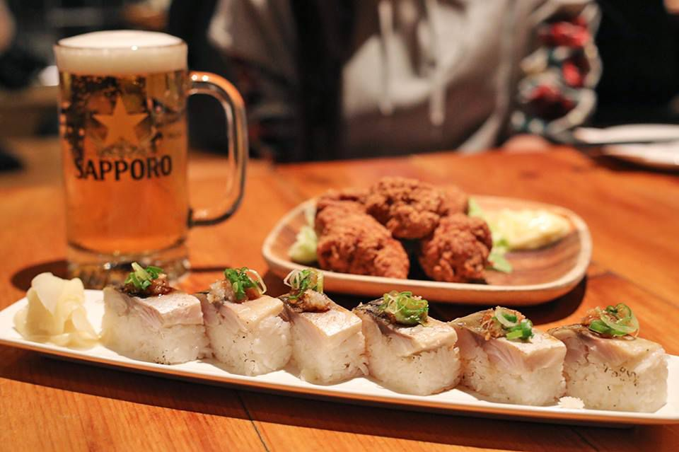 A pint of Sapporo next to a plate of Japanese fried chicken.
