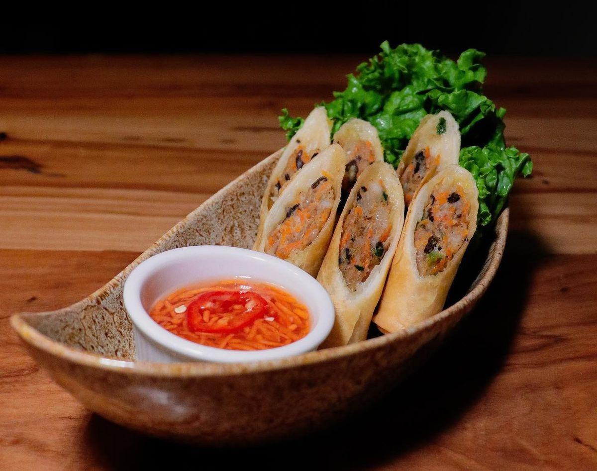 a plat of eggrolls and fish sauce dip