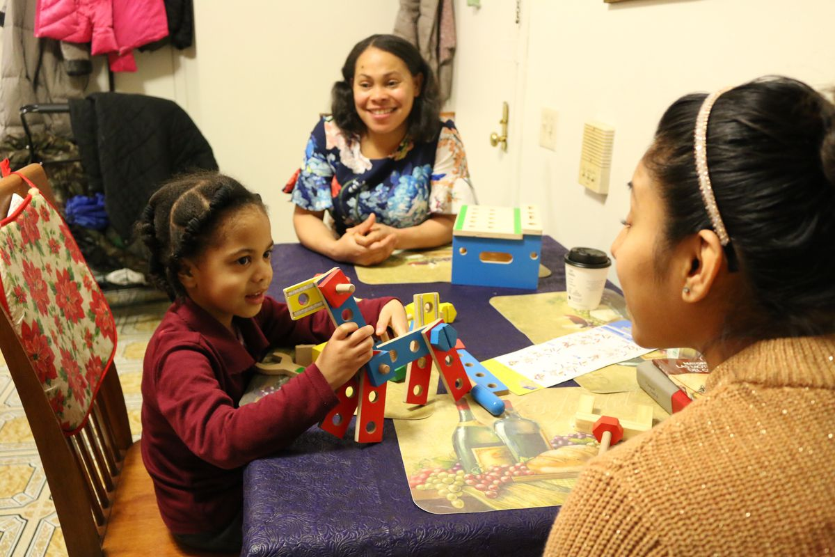 Hadasa Florian, 4, plays with a toy during a home visit with a representative from Rising Ground. The Public Prep charter network has partnered with nonprofits to visit family's homes and help parents prepare their children for school.