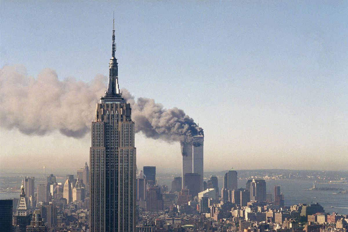 The twin towers of the World Trade Center burn behind the Empire State Building in New York, Sept. 11, 2001.