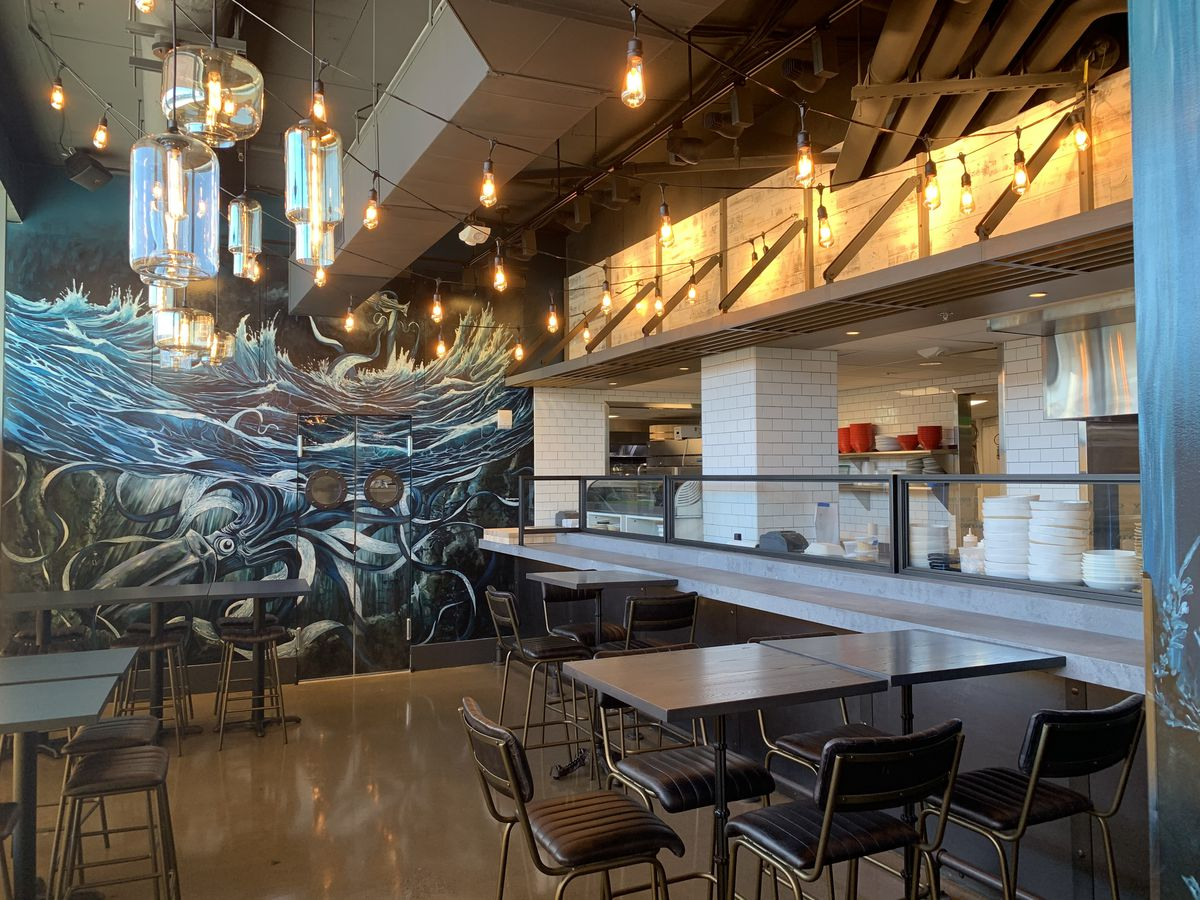 A dining room in a restaurant with a mural that features a giant squid. There is a sushi bar, and several wooden tables accompanied by leather chairs.