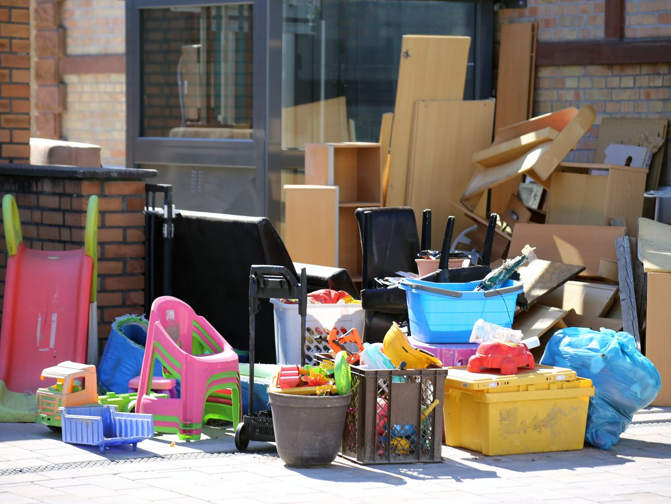 Boxes, toys, and other items on a sidewalk, in front of a building.