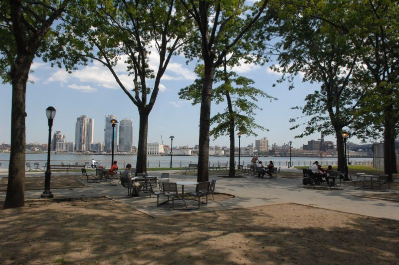 There is a park in the foreground with trees and people lounging. In the distance is a body of water and a city skyline.