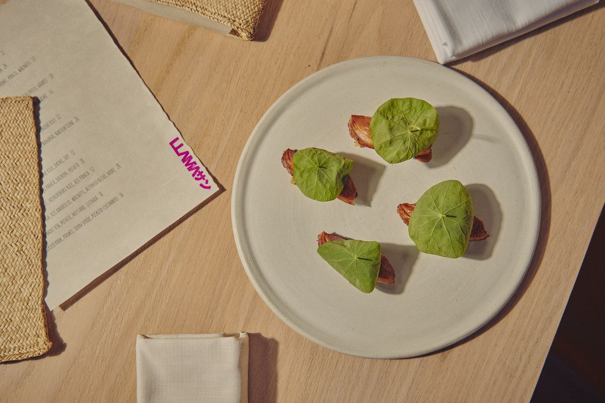Green nasturtium leaves sit over a plate of aged duck nigiri, set on a blonde wood table