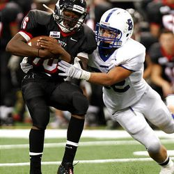 Bingham's Brandon Lambert, right, works to bring down Euless (Texas) Trinity quarterback Willie Hubbard as the Miners play Trinity in the Kirk Herbstreit Varsity Football Series Monday at Dallas Cowboys Stadium in Arlington, Texas. Trinity won 42-21.