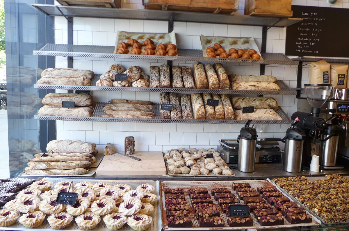 A row of Swedish pastries are lined up along a wall and in a glass shelf facing the customers.
