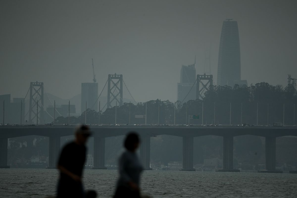 Two people silhouetted against the eastern span of the Bay Bridge and the San Francisco skyline