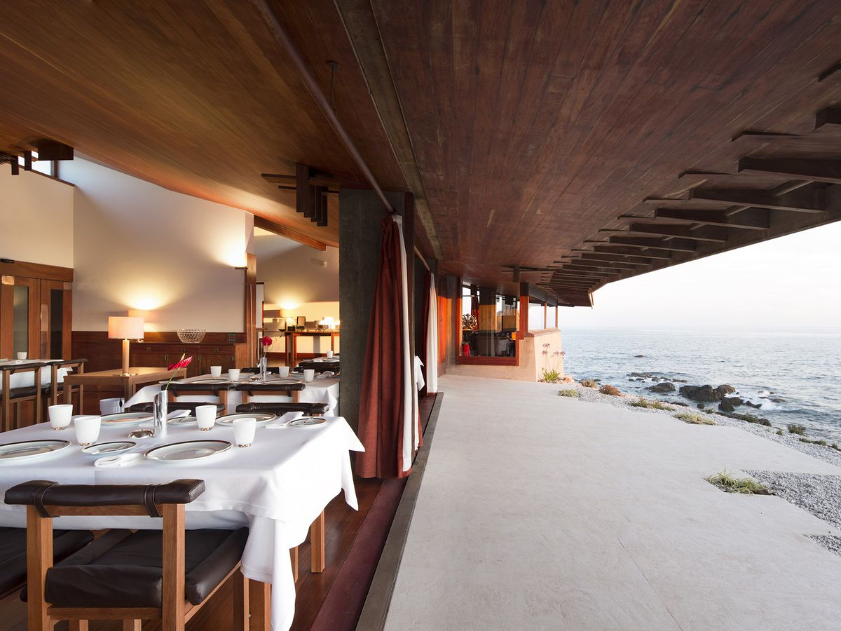 A formal dining room set inside an angular, swooping, wooden-accented facade sitting right on the sea with the ocean crashing on rocks nearby