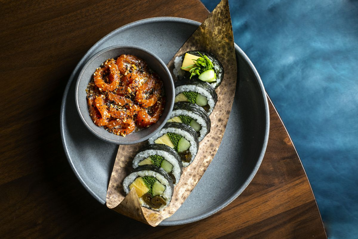 A sliced kimbap roll laid out on a plate with a bowl of salmon set next to it